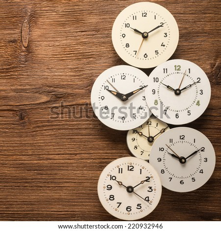Simple round clock on a wooden background   - stock photo