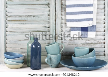 Simple rustic kitchen still life: blue ceramic dish, bowls, mugs, glass bottles and towels against shabby wooden shutters.