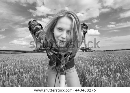 Simple teen girl on a bicycle in a summer field - stock photo