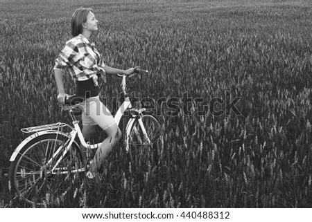 Simple teen girl on a bicycle in a summer field