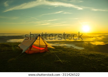 Simple Tent on the Top of a green mountain with the Sunrise - stock photo