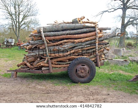 Simple tractor trailer with stacked firewood logs.       - stock photo