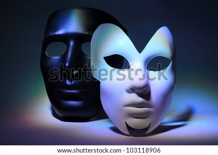 simple white serious mask and black mask, which is colorful highlighted - stock photo