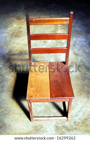 Simple wooden chair in a dark room illuminated by natural light from above - stock photo