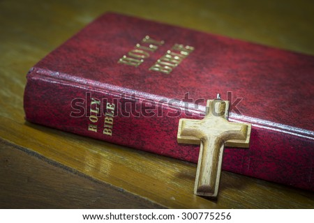 simple wooden Christian cross and the red holy Bible on wooden background