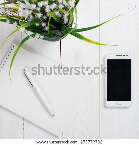 Simple workspace on wooden table on which there is a smartphone and a notebook with a ballpoint pen. - stock photo