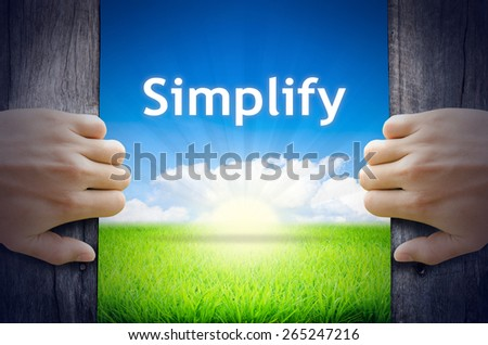 Simplify. Hands opening a wooden door then found a texts floating among new world as green grass field, Blue sky and the Sunrise. - stock photo