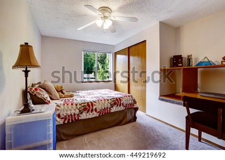 Simplistic and cozy bedroom interior with colorful bedding and built-in wardrobe. Also small home office area with laptop. - stock photo