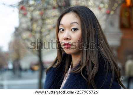 simpotichnoy portrait asian girl in a coat with a fur collar - stock photo