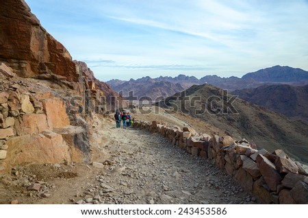 SINAI MOUNTAINS, EGYPT - NOVEMBER 28, 2013: Tourists descend on the long trail to Mount Moses, Egypt - stock photo