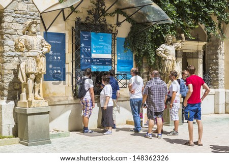 SINAIA, ROMANIA - JULY 24: Unidentified group of tourists wait in line to buy tickets for guided visiting tour at famous Peles castle on July 24, 2013 in Sinaia, Romania. - stock photo