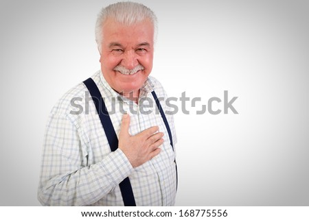 Sincere senior man with his hand on his heart looking at the camera with a warm friendly smile, upper body studio portrait on grey with copyspace - stock photo