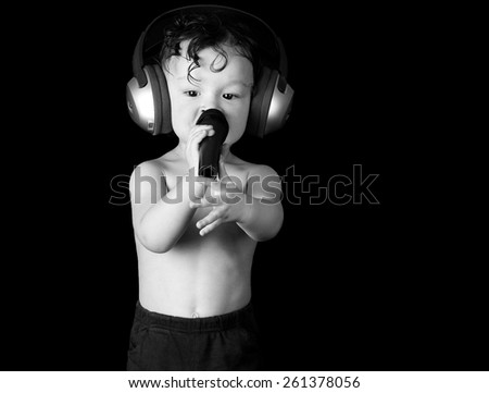 Sing baby with headphone and microphone, on a black background. - stock photo