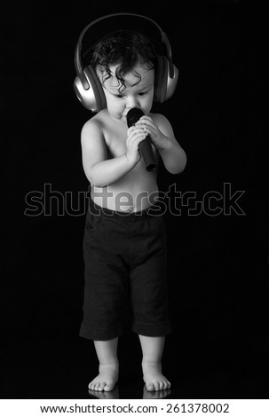 Sing baby with headphones and microphones, on a black background. - stock photo