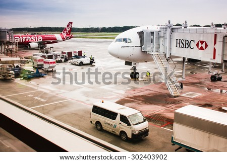 SINGAPORE AIRPORT, SINGAPORE - DECEMBER 6, 2014: Boeing 777 300 ER with HSBC passenger tunnel and Air Asia airplane standing on wet Singapore airport ground after rain - passenger terminal window view - stock photo