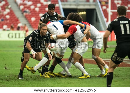 SINGAPORE-APRIL 16: France 7s Team (white) plays against New Zealand 7s team (black) during Day 1 of HSBC World Rugby Singapore Sevens on April 16, 2016 at National Stadium in Singapore