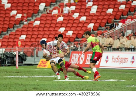SINGAPORE-APRIL 16: Japan 7s Team (white/red) plays against Portugal 7s team (green) during Day 1 of HSBC World Rugby Singapore Sevens on April 16, 2016 at National Stadium in Singapore