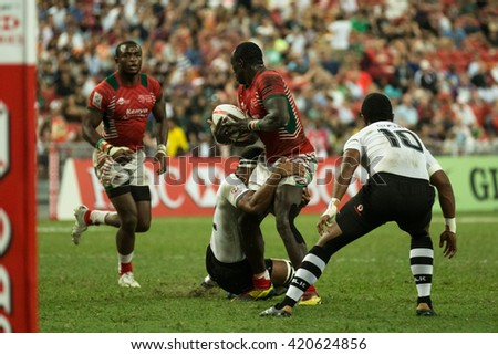 SINGAPORE-APRIL 17:Kenya 7s Team (red) plays against Fiji 7s team (white) during Day 2 of HSBC World Rugby Singapore Sevens on April 17, 2016 at National Stadium in Singapore