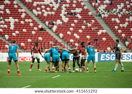 SINGAPORE-APRIL 16: Kenya 7s Team (red) plays against Russia 7s team (blue) during Day 1 of HSBC World Rugby Singapore Sevens on April 16, 2016 at National Stadium in Singapore