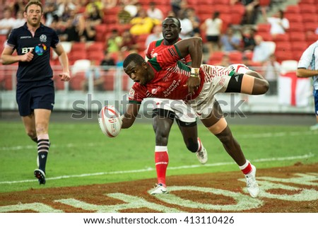 SINGAPORE-APRIL 16: Kenya 7s Team (red) plays against Scotland 7s team (navy blue) during Day 1 of HSBC World Rugby Singapore Sevens on April 16, 2016 at National Stadium in Singapore - stock photo
