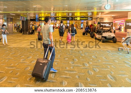 SINGAPORE- April 29 :Many passenger at International Airport on April 29, 2014. Changi Airport serves more than 100 airlines operating 6,100 weekly flights connecting Singapore to over 220 cities - stock photo
