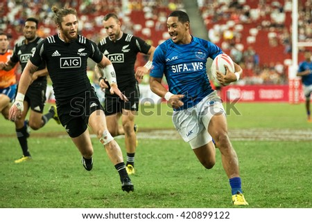 SINGAPORE-APRIL 17:New Zealand 7s Team (blue/white) plays against Samoa 7s team (blue) during Day 2 of HSBC World Rugby Singapore Sevens on April 17, 2016 at National Stadium in Singapore