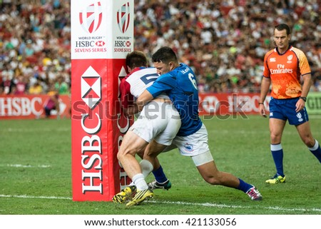 SINGAPORE-APRIL 17:Samoa 7s Team (blue) plays against France 7s team (white) during Day 2 of HSBC World Rugby Singapore Sevens on April 17, 2016 at National Stadium in Singapore