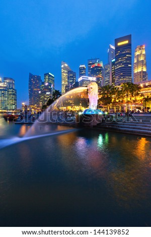 SINGAPORE - APRIL 04: The Merlion fountain in front of the Marina Bay Sands hotel on April 04, 2013 in Singapore. Merlion is a imaginary creature with the head of a lion, seen as a symbol of Singapore - stock photo