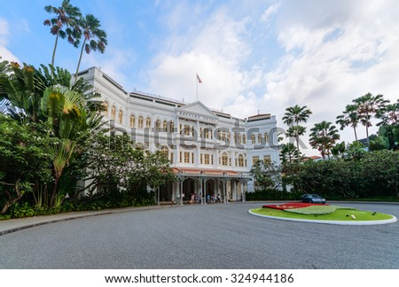 SINGAPORE - 07 AUG 2015: Grand facade of the luxurious Raffles Hotel in downtown Singapore, with its beautiful gardens. - stock photo