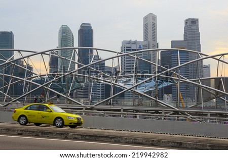 SINGAPORE - AUGUST 23, 2014: Taxi passes along pedestrian The Helix Bridge. Bridge won the 'World's Best Transport Building' award at the World Architecture Festival in the 2011. - stock photo