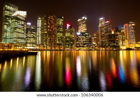 Singapore business district in the night time with water reflections - stock photo