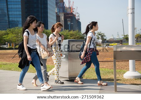 SINGAPORE - CIRCA FEBRUARY, 2015: Group of young girls walking along the waterfront Marina Bay in Singapore. Quay Marina Bay is a popular place for walks among the tourists and locals.