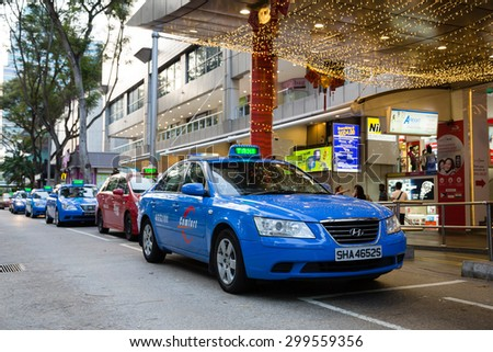 SINGAPORE - CIRCA FEBRUARY, 2015: Taxi to Orchard Road. Singapore more than 25 thousand cars involved in carting passengers, taxi is an important and popular form of public transport. - stock photo