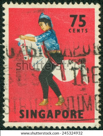 SINGAPORE - CIRCA 1968: Red color postage stamp printed in Singapore with image of a traditional Kuda Kepang dancer on a horse prop.CIRCA 1968 - stock photo
