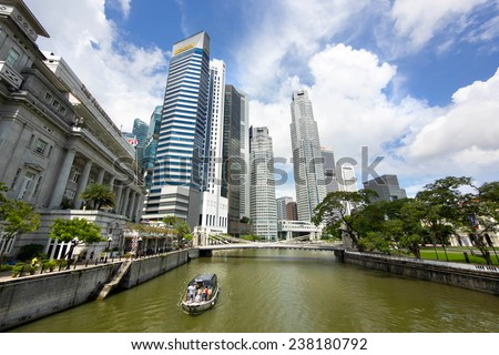 Singapore City, Singapore - June 1, 2014: View of tourist boat floating on Singapore river with downtown buildings in the background on June 1, 2014, in Singapore City, Singapore.  - stock photo