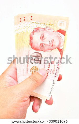 Singapore currency in hand isolated on white background. - stock photo