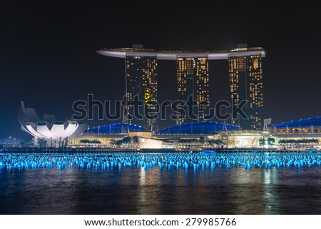 SINGAPORE - 30 DEC 2013: Singapore's skyline and Marina Bay Sands hotel and casino complex with spotlights lit up over Marina Bay before the annual New Year's Celebration. - stock photo