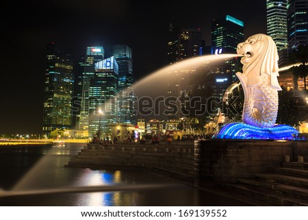 SINGAPORE-DEC 27: The Merlion fountain at night. Dec. 27, 2013  in Singapore. Merlion is an imaginary creature with a head of a lion and the body of a fish and is often seen as a symbol of Singapore.  - stock photo
