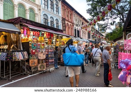 SINGAPORE - DECEMBER 12: Shoppers in Chinatown look for cheap souvenirs and bargains December 12, 2014. The old Victorian-style shop houses are a trademark of this popular area. - stock photo