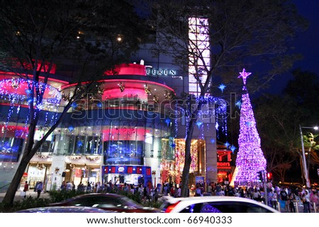SINGAPORE - DECEMBER 4: Tourists and shoppers walk along Orchard Road on December 4, 2010 Singapore. The street and buildings are decked with lights and decorative items in preparation for Christmas. - stock photo