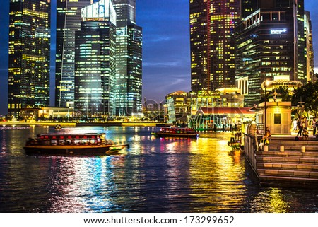 SINGAPORE - DECEMBER 15 2013: Tourists in Singapore wait by marina bay to catch a boat. - stock photo