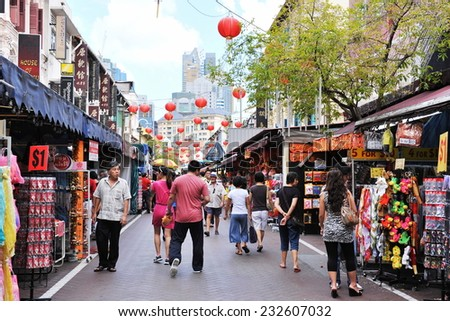 SINGAPORE - FEB 11: Shoppers walk through a Chinatown market during Chinese New Year celebrations on Feb 11, 2012 in Singapore. The city state's ethnic Chinese began settling in Chinatown circa 1820s. - stock photo