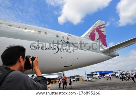 SINGAPORE - FEBRUARY 12: A photographer taking a photo of Qatar Airways Boeing 787-8 Dreamliner at Singapore Airshow February 12, 2014 in Singapore - stock photo