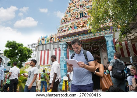 SINGAPORE - FEBRUARY 19, 2015: European tourist on background indian Hinduism temple in Little India. Little India or the Indian quarter, a very popular area with tourists visiting Singapore. - stock photo