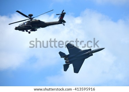 SINGAPORE - FEBRUARY 16: RSAF F-15SG fighter jet and Apache helicopter performing aerobatics at Singapore Airshow February 16, 2016 in Singapore - stock photo