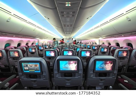 SINGAPORE - FEBRUARY 12: Spacious and comfortable economy class cabin of Qatar Airways Boeing 787-8 Dreamliner at Singapore Airshow February 12, 2014 in Singapore - stock photo