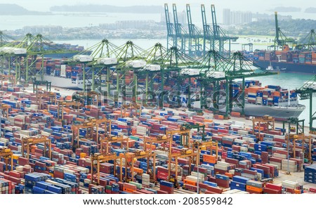 SINGAPORE - 2 JAN, 2014: Commercial port of Singapore. Bird eye panoramic view of busiest Asian cargo port with hundreds of ships loading export and import goods and thousands of containers in harbor  - stock photo