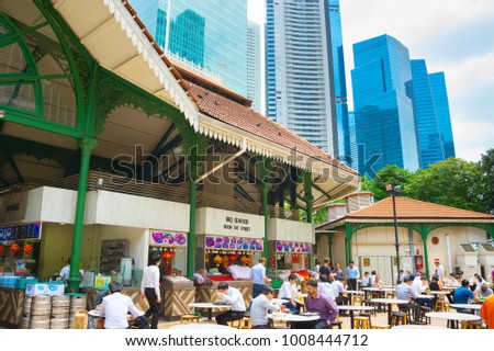 SINGAPORE - JAN 16, 2017 : People at popular food court in Singapore. Inexpensive food stalls are numerous in the city so most Singaporeans dine out at least once a day.
