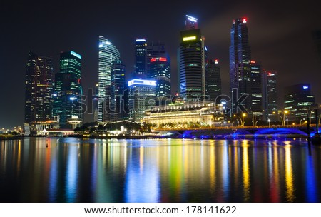 SINGAPORE-JAN 27: Singapore at night and colorful light of buildings on JAN. 27,2014.Singapore has a many of high buildings at the night and multi-color of trademarks logo at the top of building - stock photo