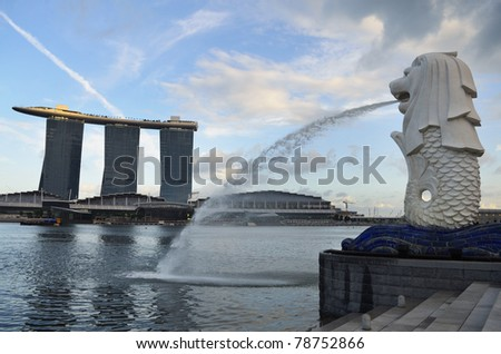 SINGAPORE-JAN 25:The Merlion fountain spouts water infront of Singapore skyline Jan 25, 2011. It's an imaginary creature with head of lion and body of fish and often seen as a symbol of Singapore. - stock photo